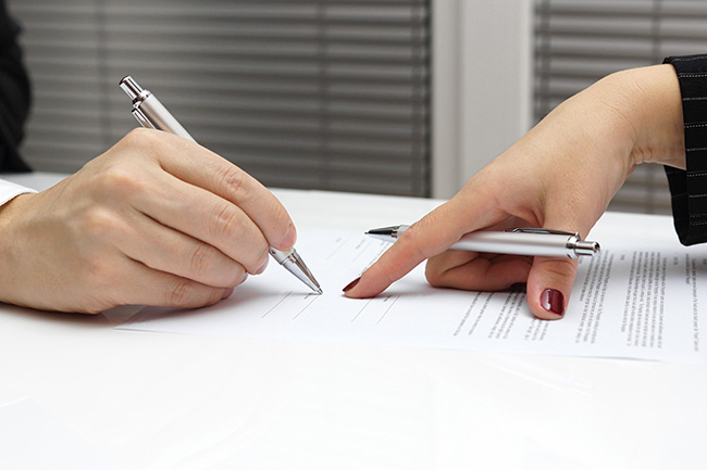 photo of a lawyer instructing her client where to sign his settlement agreement after resolving his divorce negotiations with his spouse