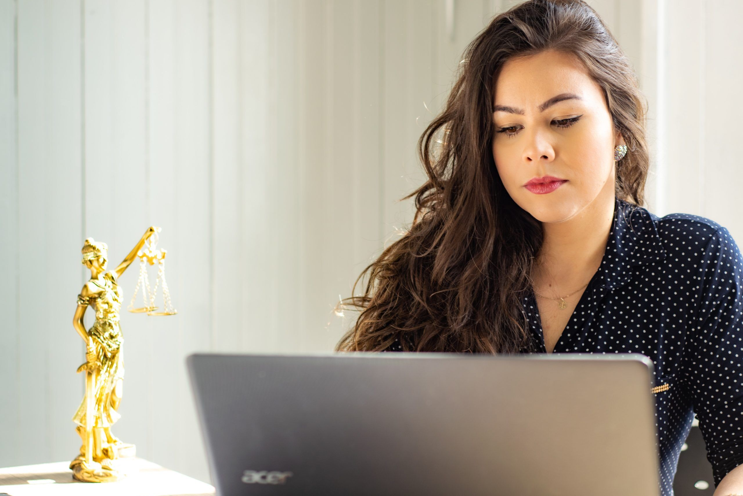 Woman lawyer on computer with lady justice